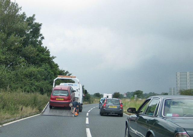 A broken down car on a recovery vehicle